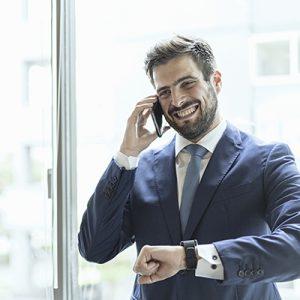 ビジネスマンがスマートフォンとスマートウォッチを使っている