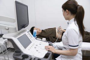 病院で腹部エコー検査を受ける男性