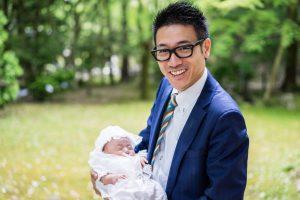 お宮参りで子供を抱く父親