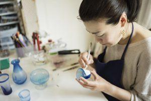 ガラスに絵付けをする女性アーティスト
