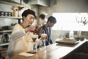 カフェでコーヒーを淹れる女性