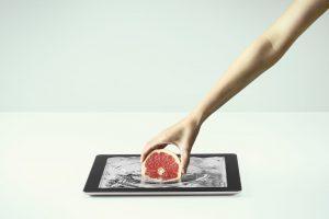 タブレット画面から果物を取り出す手