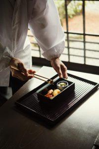 料亭の和食の料理人が料理の盛り付けをしている