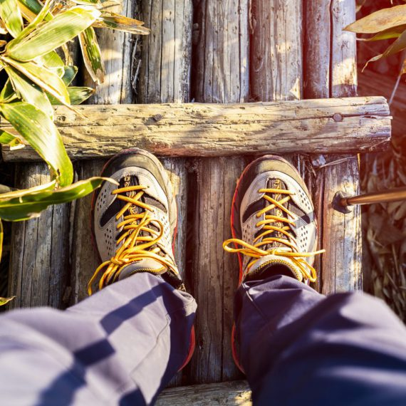 登山で木の橋を歩く男性の足元