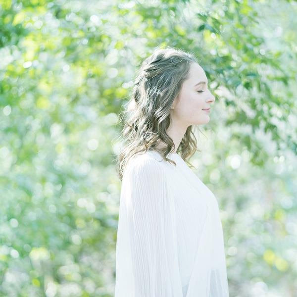緑の中で目を閉じてほほ笑む女性の横顔