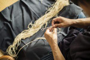職人が糸を紡いでいる