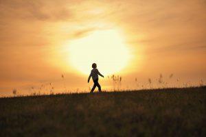 夕焼けの土手を歩く女性