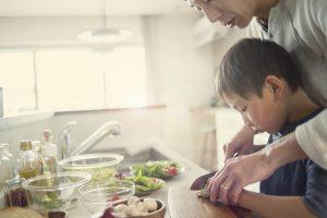 台所で料理をする父親と男の子