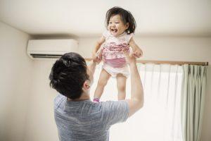高い高いをする父親と娘