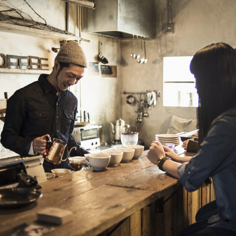 客と談笑するカフェオーナー
