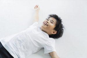 ダンスの休憩中に床に寝転がる笑顔の男の子