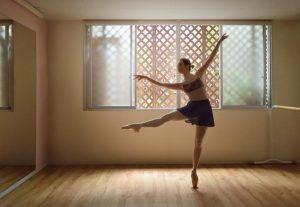 部屋でバレエを踊る女性バレリーナ