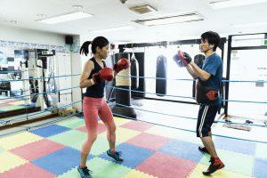ボクシングジムでスパーリングをする女性と男性コーチ