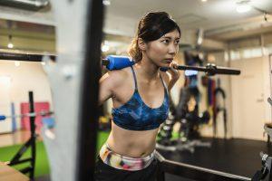 バーベルをもってスクワット運動をする女性