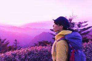 山の上で綺麗な夕景を楽しむ女性のハイカー