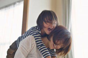 自宅で母に抱きつくおさない娘