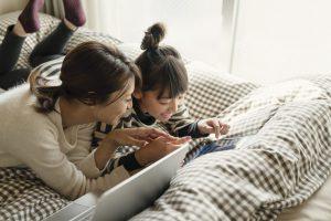 ベッドでくつろいでタブレットを使う母と娘