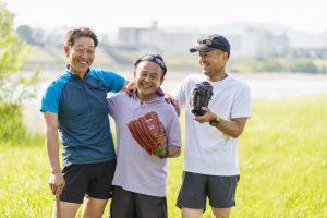 河川敷の広場で笑顔で運動をするシニア男性3人