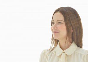 スタジオの白い背景で撮影した笑顔の女性