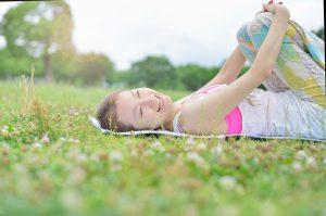 芝生でヨガを楽しむ女性のヨガインストラクター