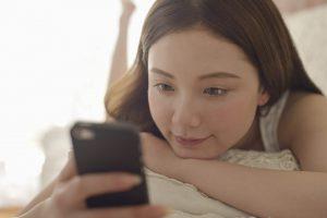 女性が部屋でくつろぎながらスマートフォンを使用している写真