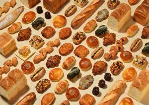 ベージュの背景に様々なパンを並べた写真